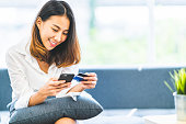 Young beautiful Asian woman using smartphone and credit card for online shopping at home with copy space. E-payment technology, shopaholic lifestyle, or mobile phone financial application concept