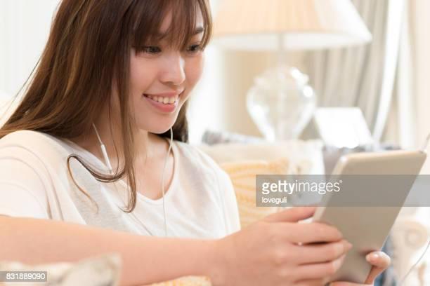 デジタル タブレットを持つ若い美しいアジア女性