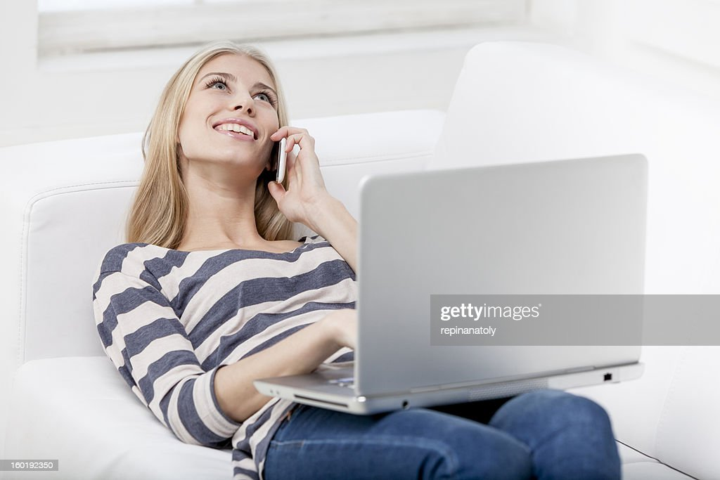 young beautiful blond woman laying on the couch with laptop : Stock Photo