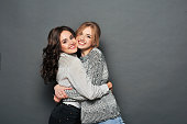 young beautiful brunette and blond haired girls hugs in front of gray background