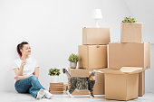 A young beautiful brunette girl in a white T-shirt is sitting on the floor of a bright room and making calls on her smartphone. Around cardboard boxes and a cat. The concept of moving to a new home.