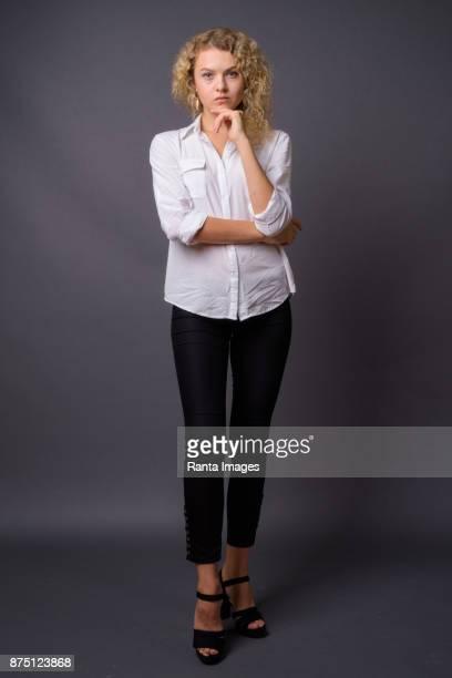 Junge schöne Geschäftsfrau mit blonden lockigen Haaren vor grauem Hintergrund