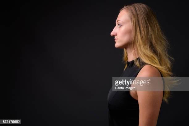 Junge schöne Geschäftsfrau mit gerade blonden Haaren vor grauem Hintergrund