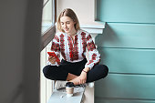 Young beautiful caucasian girl student wearing a vyshyvanka, a traditional Ukrainian embroidered shirt checks her smartphone while drinking coffee between lectures