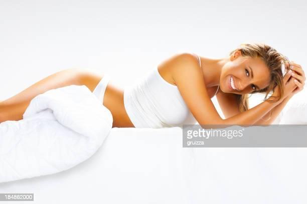 Junge, schöne, fröhlich blonde Frau entspannend auf Bett
