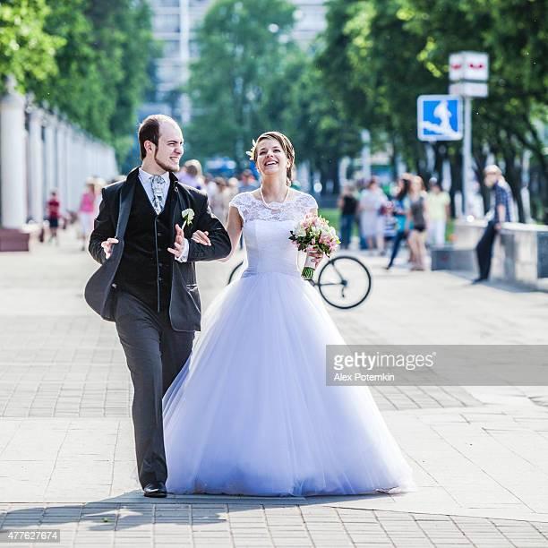 Jeune beau couple, le marié et la mariée, marcher sur la rue