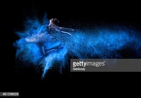 Young beautiful dancer jumping into blue powder cloud : Stock Photo