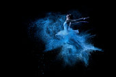 Young beautiful dancer jumping into blue powder cloudYoung beautiful dancer jumping into blue powder cloud
