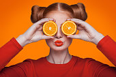 Young beautiful funny fashion model with orange slice on orange background. with orange makeup and hairstyle and freckles. holding orange between eyes with kiss.