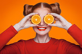 Young beautiful funny fashion model with orange slice on orange background. with orange makeup and hairstyle and freckles. holding orange between eyes with toothy smile.