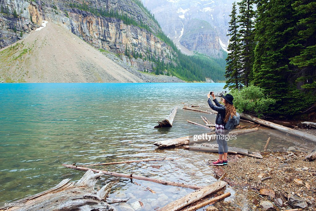 Young beautiful female backpacker doing pictures on her phone : Stockfoto