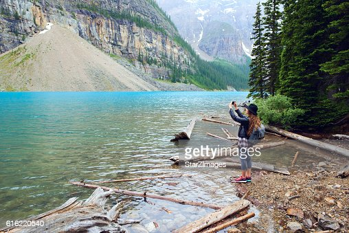 Young beautiful female backpacker doing pictures on her phone : Foto stock