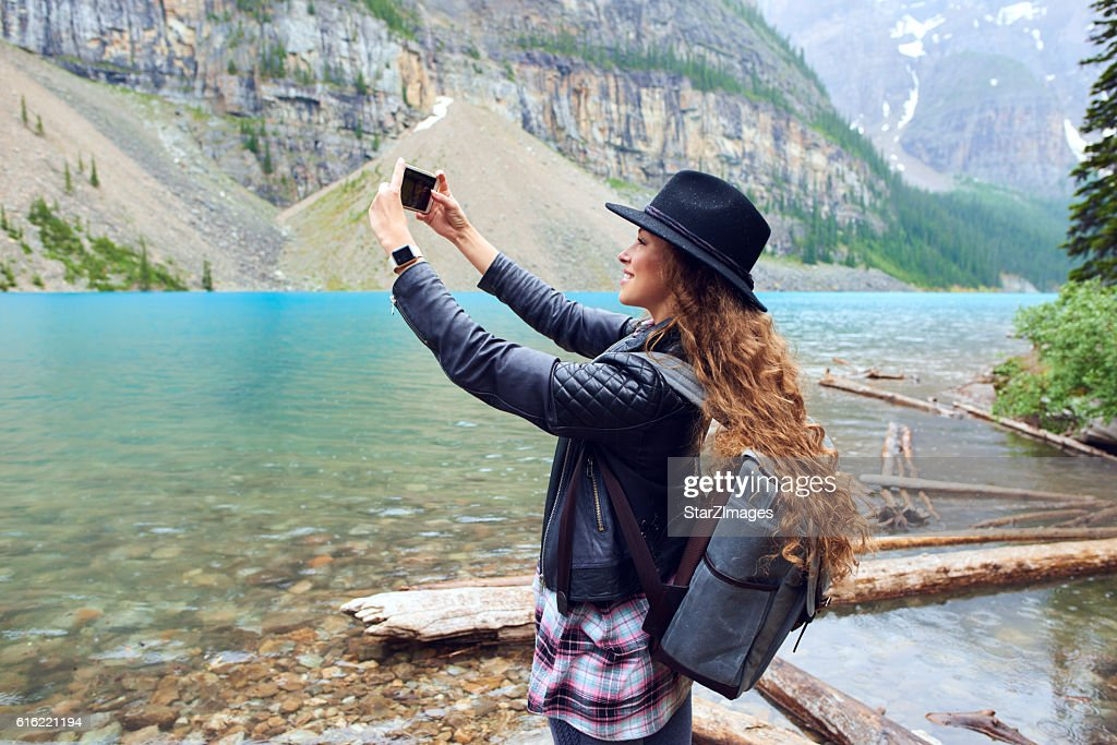 Young beautiful female backpacker doing pictures on her phone : Stock-Foto