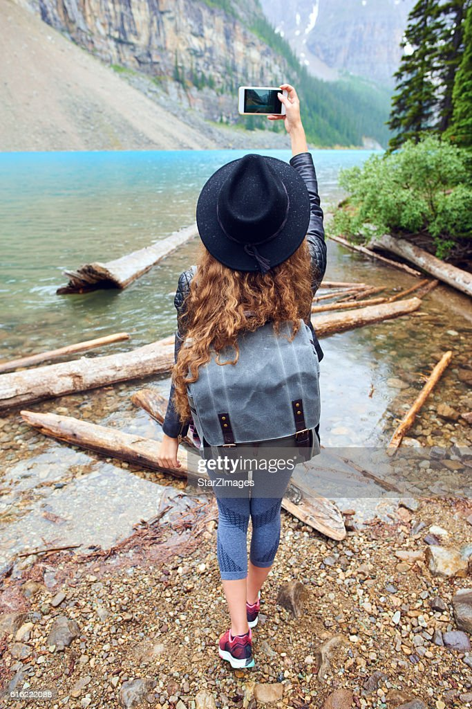 Young beautiful female backpacker doing pictures on her phone : Photo