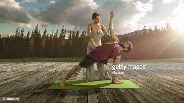 Young beautiful female yoga teacher teaches man assan
