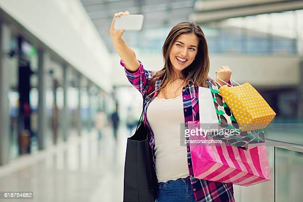 Young beautiful girl is taking selfie in the Mall