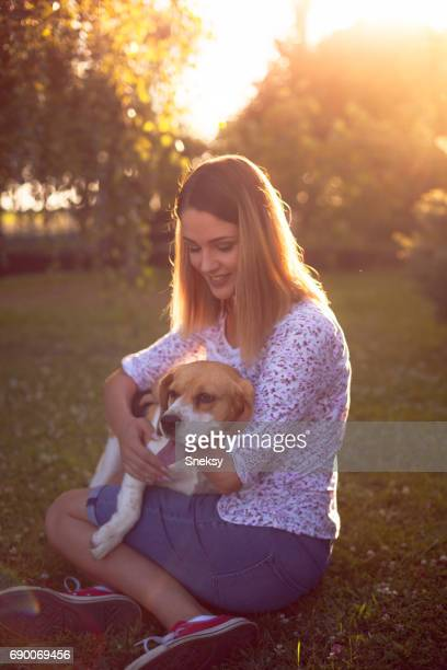 Young beautiful girl playing with her dog at sunset