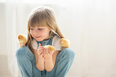 Young beautiful girl, playing with little newborn chick at home, isolated on white