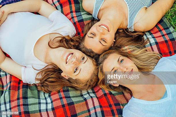 Young beautiful girlfriends lying on blanket in park