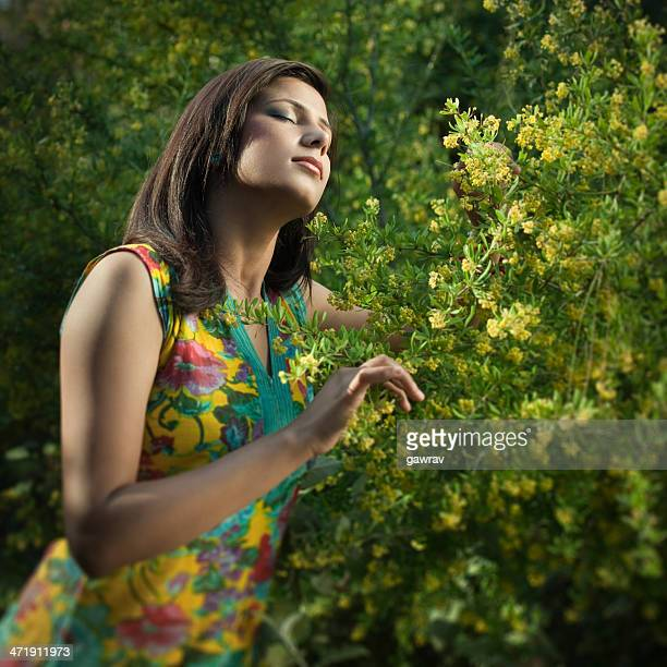 Young, beautiful Indian woman feeling fresh fragrance in blossoming nature.