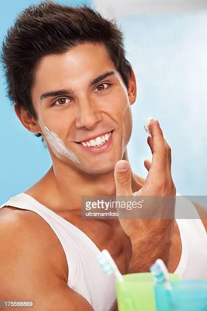 Young beautiful man applying cream