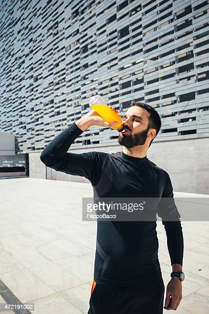 Young Beautiful Man Drinking An Energy Drink While Training