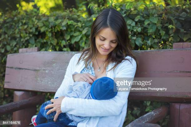 Young beautiful mother sits on bench, breastfeeding her newborn baby boy in the park