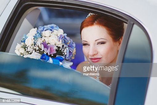 young beautiful red bride with bouquet in garden : Stock Photo