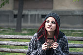 Young beautiful red hair girl sitting alone outdoors on the wooden bench with hat and shirt feeling anxious and depressed after she became a homeless person close up portrait