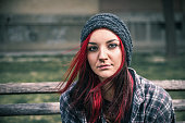 Homeless girl, Young beautiful red hair girl sitting alone outdoors on the wooden bench with hat and shirt feeling anxious and depressed after she became a homeless person close up portrait