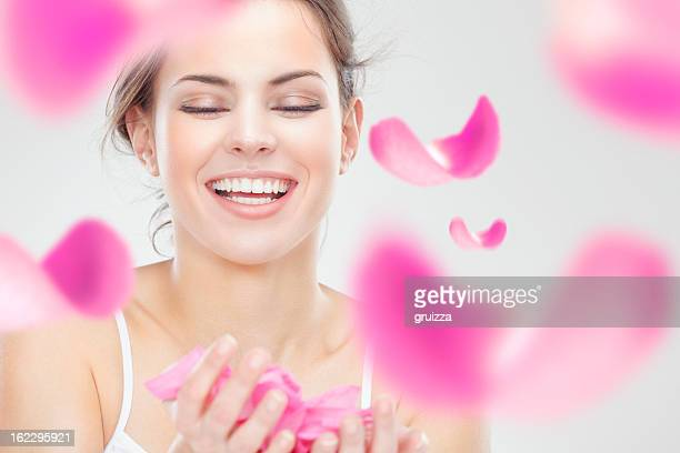 Young beautiful smiling woman surrounded by flying pink rose petals