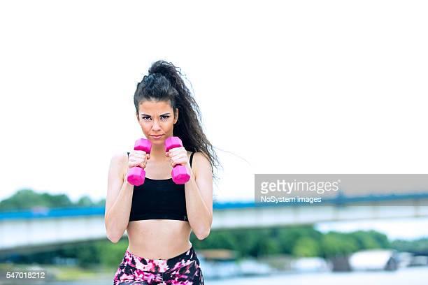 Sport giovane bella ragazza con manubri