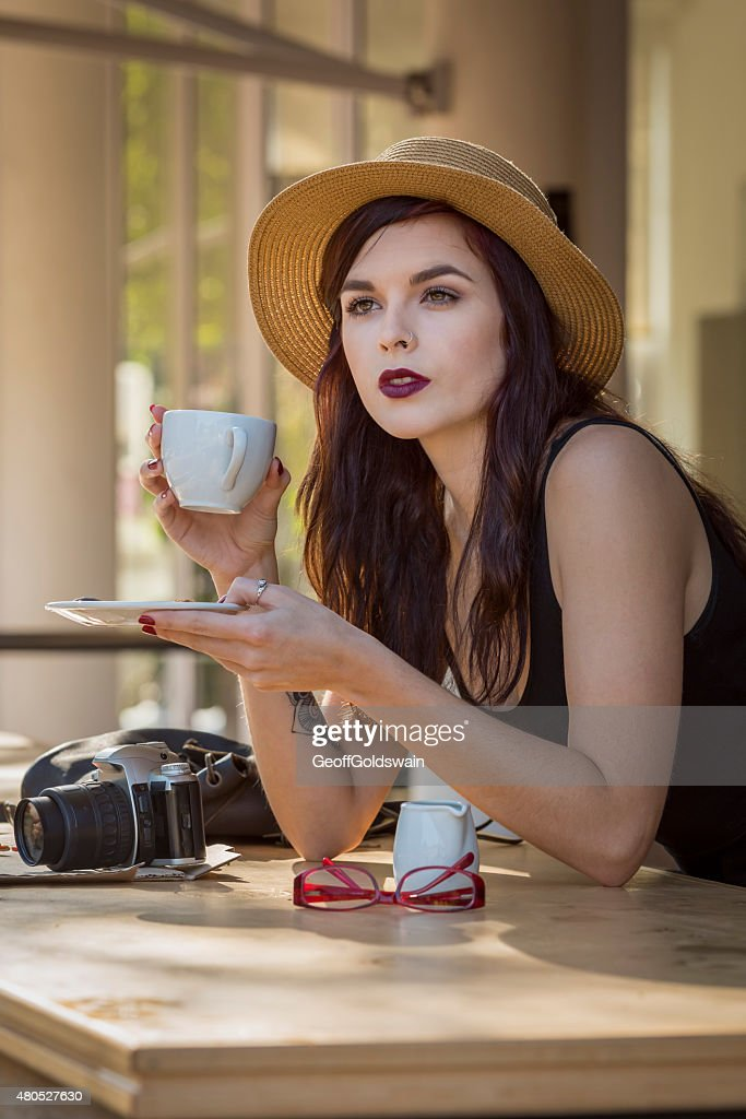 young beautiful traveler enjoying a coffee at street cafe : Stock Photo