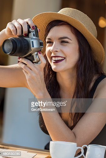 young beautiful traveler happily taking photos with camera at ca : Stock Photo