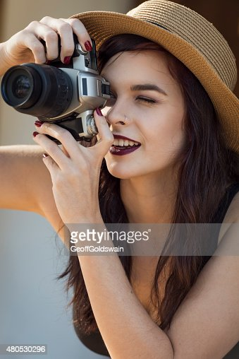 young beautiful traveler happily taking photos with camera at ca : Bildbanksbilder