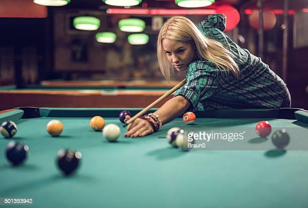 Junge schöne Frau Zielen im pool ball in einem pub.