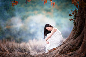Young beautiful woman alone sitting under tree indian summer style vintage concept
