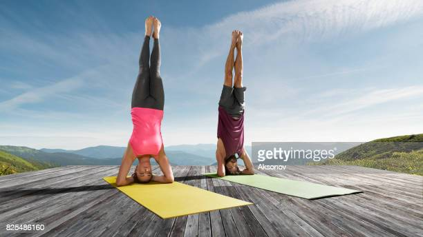 Young beautiful woman and man practicing outdoors yoga