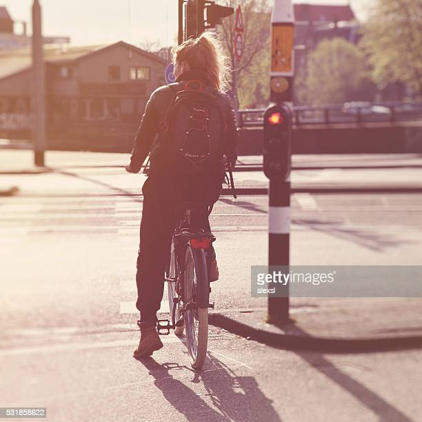 Young beautiful woman commuter riding a bicycle in Amsterdam