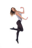 young beautiful woman dancer with long black hair wearing gray vest and tights jumping on a light white studio background