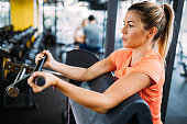 Young beautiful woman doing exercises for biceps in gym