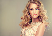 Young beautiful woman, dressed in evening gown. Loose,wavy hair and bright make up. Straight look on camera.