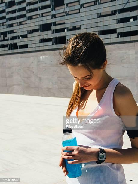 Joven hermosa mujer disfruta de una bebida energética y capacitación