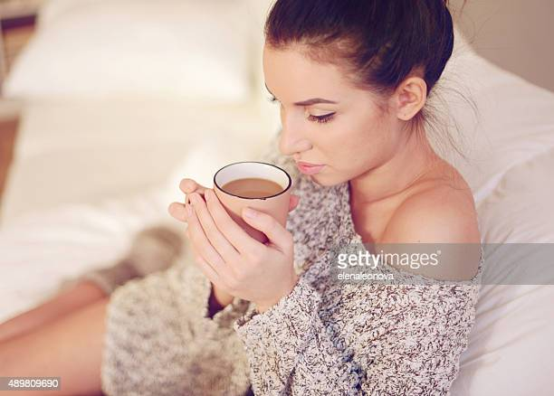 young beautiful woman drinking hot coffee close-up