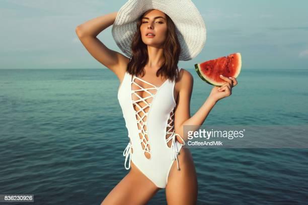 Young beautiful woman eating watermelon at summer beach