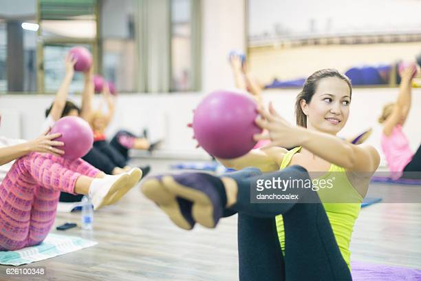 Young beautiful woman exercising pilates with ball