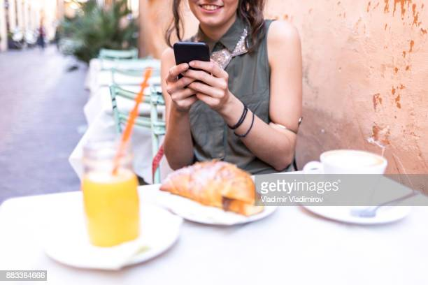 Young beautiful woman having breakfast in Rome