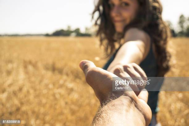 Young beautiful woman holding her boyfriend's hand on a field of grain