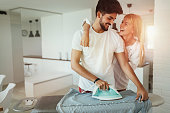 Young beautiful woman hugging her attractive boyfriend while he uses iron