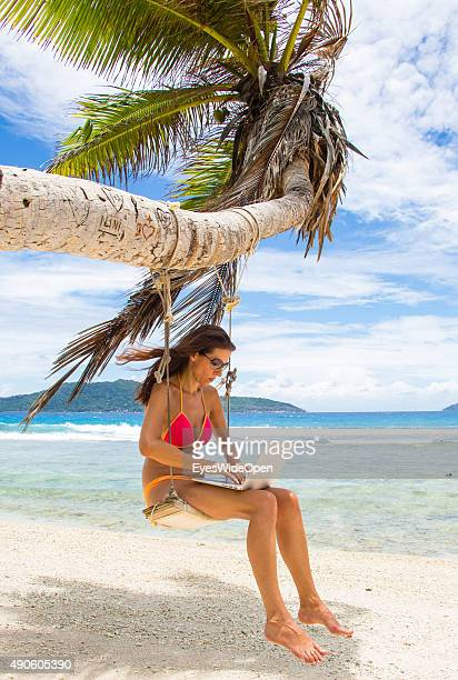 Young beautiful woman in a bikini swinging and working with a laptop computer at a palmtree at white sandy Banana Beach on September 27 2015 in La...